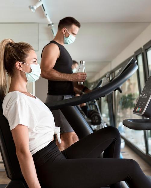 Man en vrouw trainen in de sportschool met medische maskers Gratis Foto