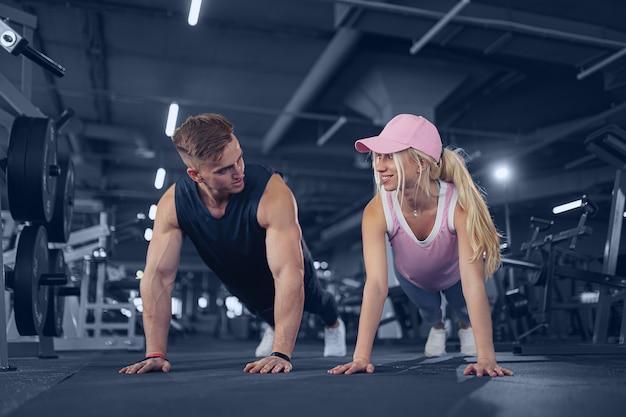 Man en vrouw versterken handen bij fitnesstraining. geschiktheidsjongeren die opdrukoefeningen in een gymnastiek doen die gezichts gelukkige oefening kijken Premium Foto