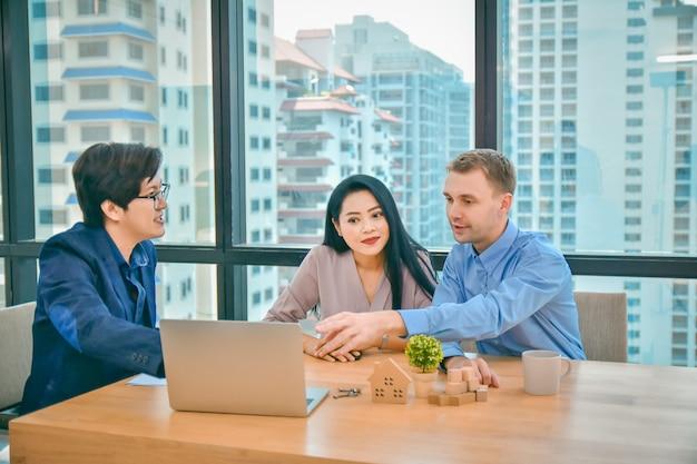 Man en vrouw zijn in gesprek met een verkoper van een residentieel condominium. raadpleging een huis en woning kopen. Premium Foto