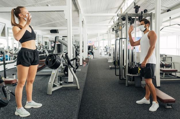 Man en vrouw zwaaien naar elkaar in de sportschool Gratis Foto