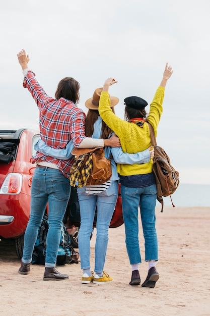 Man en vrouwen die dichtbij auto op overzees strand omhelzen Gratis Foto
