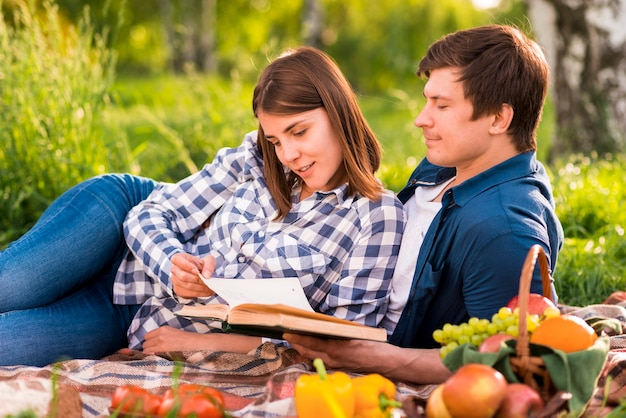 Man en vrouwenlezingsboek op picknick Gratis Foto