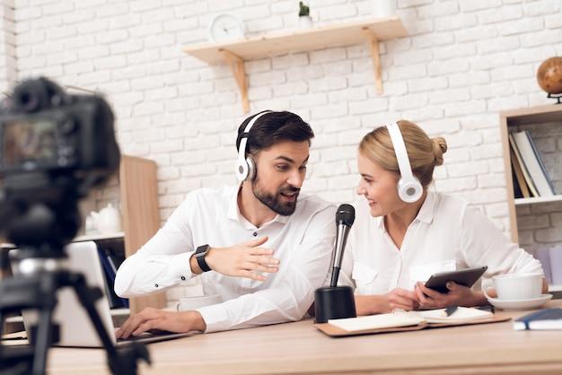 Man en vrouwenpodcasters die bij camera voor radiopodcast stellen. Premium Foto
