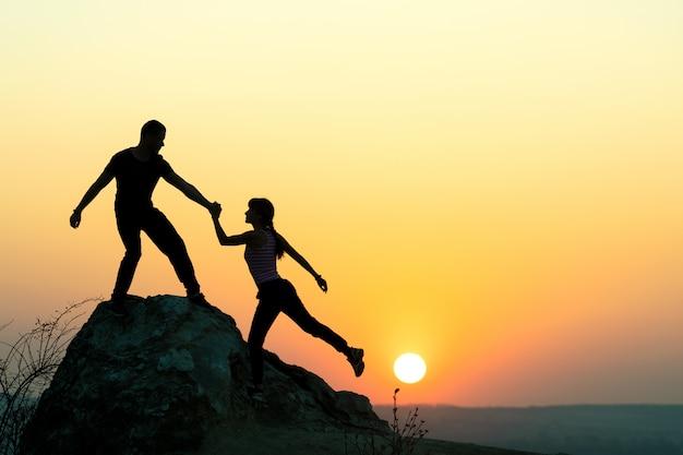 Man en vrouwenwandelaars die elkaar helpen om een grote steen te beklimmen bij zonsondergang in bergen. paar klimmen op een hoge rots in de avond de natuur. toerisme, reizen en een gezonde levensstijl concept. Premium Foto