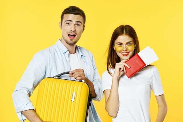 Man en vrouwreiziger met een koffer, gekleurde achtergrond, vreugde, paspoort Premium Foto