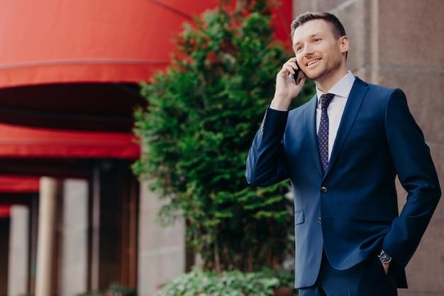 Man executive in formele pak, heeft telefoongesprek via slimme telefoon Premium Foto