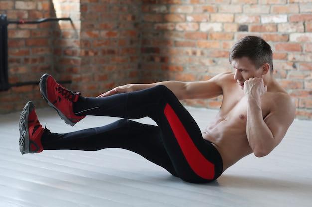 Man fitnesstraining. shirtless mens die thuis het uitrekken doen zich Gratis Foto