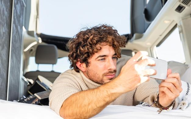 Man fotograferen met smartphone vanuit de auto tijdens een roadtrip Gratis Foto