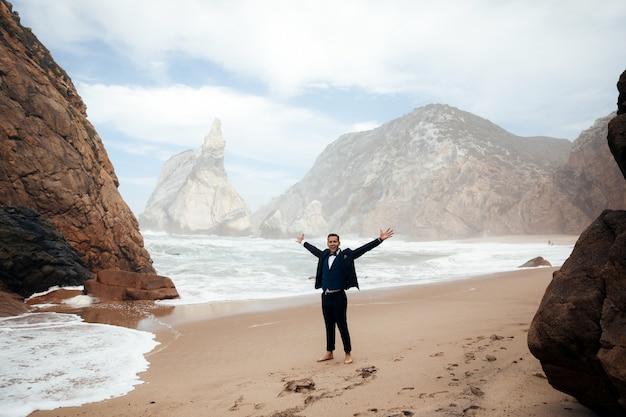 Man gekleed in het pak staat op het strand tussen de rotsen en hij ziet er gelukkig uit Gratis Foto