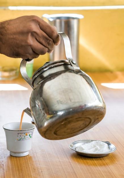 Man gieten chai thee in een beker Premium Foto