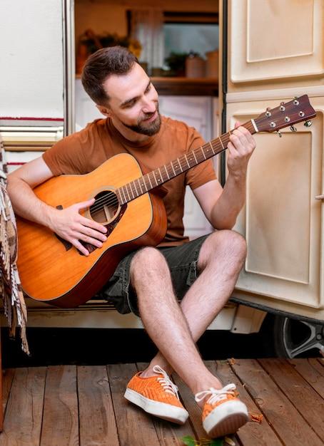 Man gitaarspelen buiten zijn busje Gratis Foto