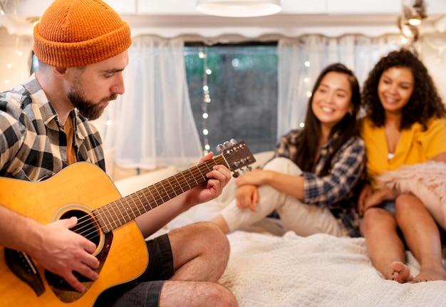 Man gitaarspelen en vrouwen luisteren Gratis Foto