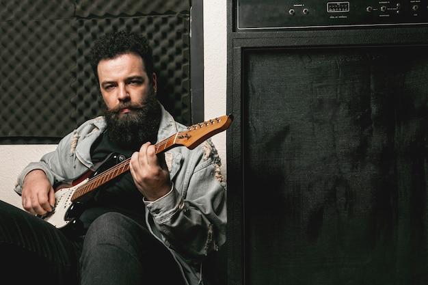 Man gitaarspelen naast versterker Gratis Foto