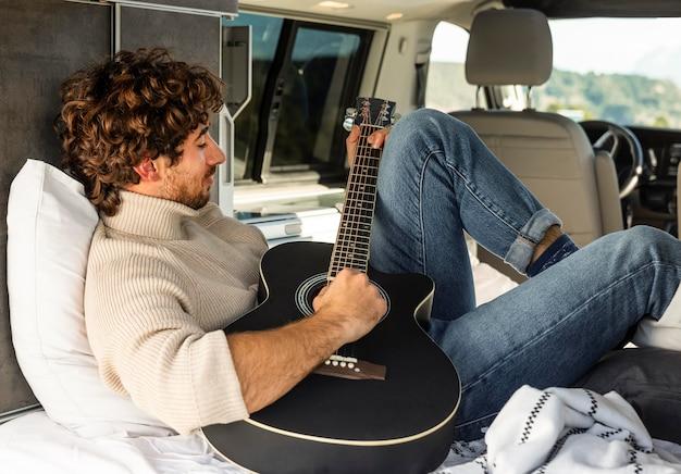 Man gitaarspelen uit auto tijdens een road trip Gratis Foto