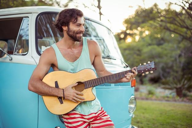 Man gitaarspelen voor camper op camping Premium Foto