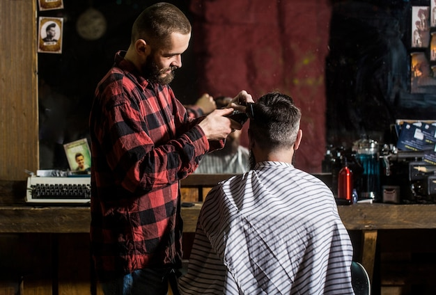 Man haarstylist. kapper knippen haar van mannelijke klant. haarstylist die klant bedient bij de kapper. Premium Foto