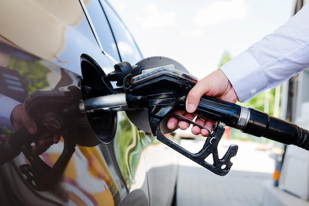 Man hand bijtankende auto bij benzinepost Gratis Foto