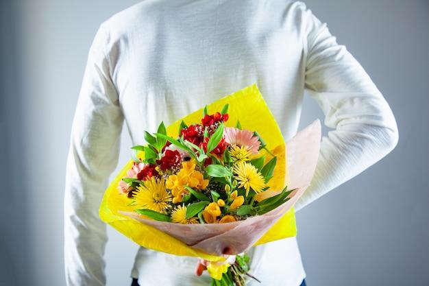 Man hand bloemen boeket in de rug Premium Foto