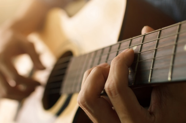 Man hand die akoestische gitaar, muzikaal concept speelt Premium Foto