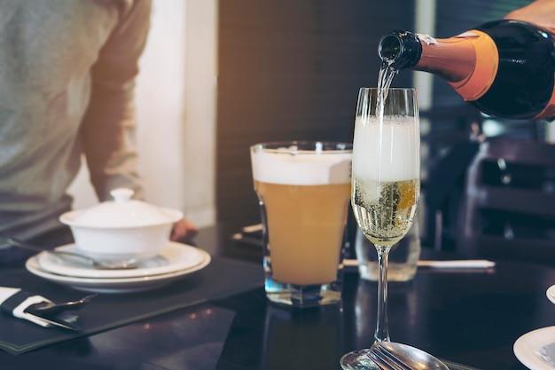 Man hand gieten champagne in glas klaar om te drinken over vervagen tabel in restaurant Gratis Foto