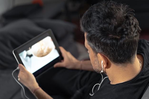 Man hand hebt met behulp van digitale tablet kijken naar online koken masterclass met koptelefoon. op afstand leren koken Premium Foto