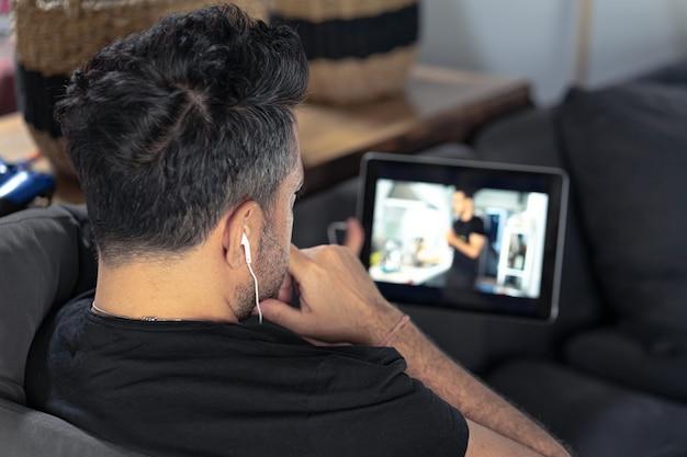 Man hand hebt met behulp van digitale tablet kijken naar online koken masterclass Premium Foto