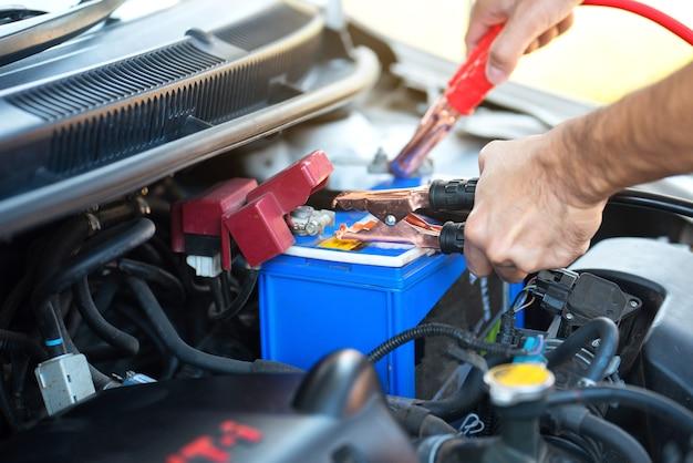 Man hand met batterij opladen kabels overbrengen van de macht om een lege batterij Premium Foto