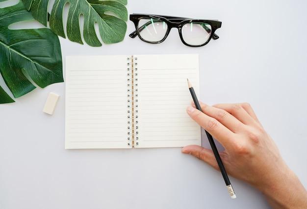 Man hand met zwart potlood en bereid om te schrijven op mock-up notebook in bovenaanzicht Premium Foto