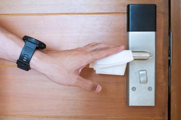 Man hand schoonmaken van digitale deurklink door vochtig af te vegen weefsel, bescherming coronavirus of corona virus disease (covid-19) in openbare ruimte. schoon oppervlak, levensstijl, veiligheidsreizen en nieuw normaal concept Premium Foto