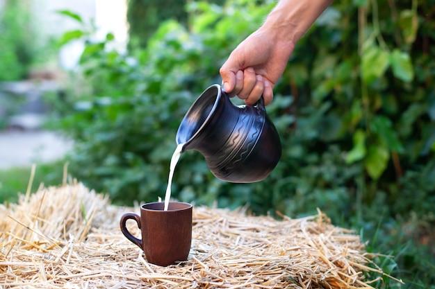 Man hand stroomt melk van kleikruik in kop op een hooiberg op gebied. biologische melk en rustieke stijl. Premium Foto