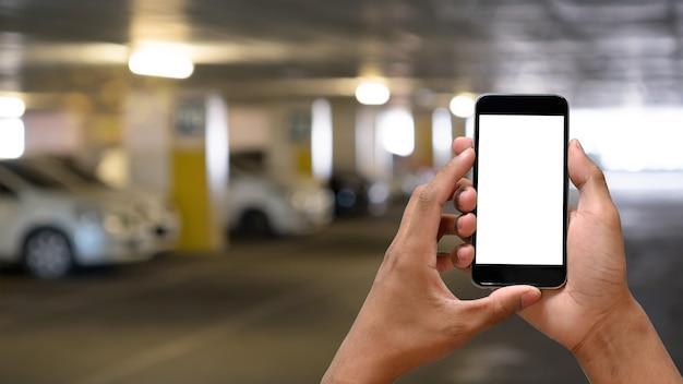 Man handen die het smartphone lege scherm in autoparkeren houden. Premium Foto