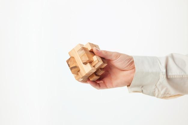 Man handen die houten raadsel houden. Gratis Foto