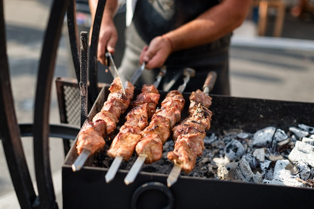 Man handen koken vlees op een barbecue Premium Foto