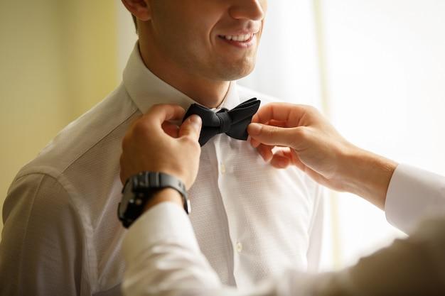 Man helpt bij het aankleden van een stropdas Premium Foto