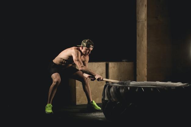 Man hits tire. training bij gym met hamer en tractorband siluet Premium Foto