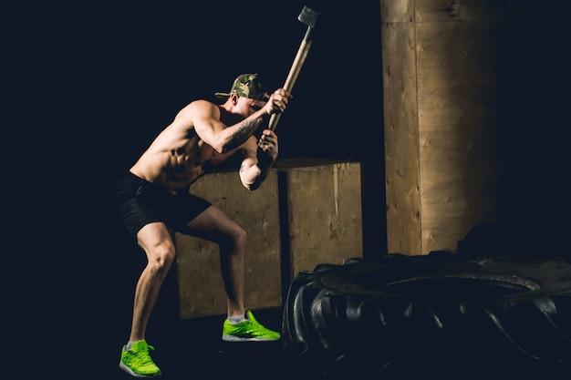 Man hits tire. training bij gym met hamer en tractorband Premium Foto