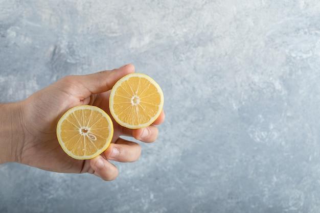 Man houdt half gesneden verse, sappige citroenen. hoge kwaliteit foto Gratis Foto