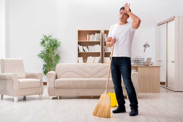 Man huis met bezem schoonmaken Premium Foto