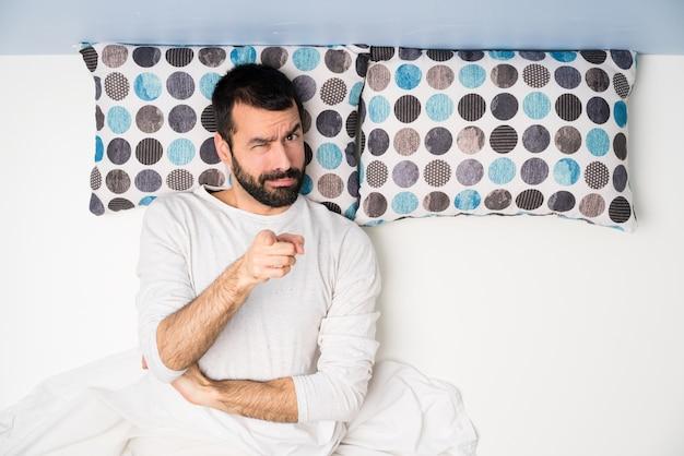 Man in bed in bovenaanzicht gefrustreerd en wijzend op de voorkant Premium Foto