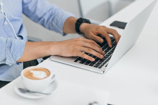 Man in blauw shirt met behulp van laptop voor werk, typen op toetsenbord. indoor portret van mannelijke handen op computer en kopje koffie op tafel. Gratis Foto