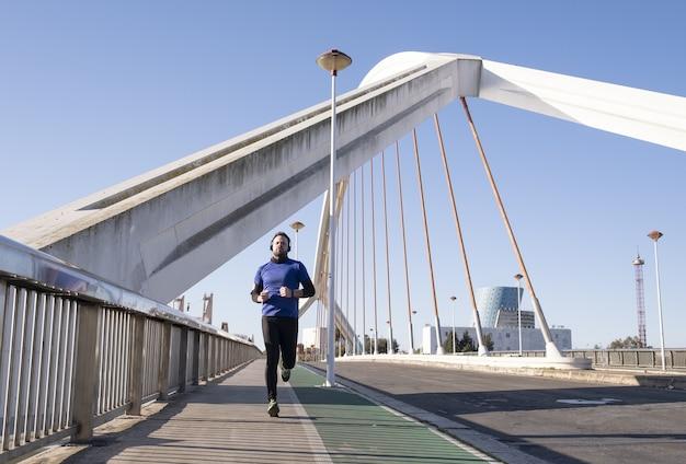 Man in blauwe koptelefoon met zijn gsm tijdens het joggen in de straat Gratis Foto