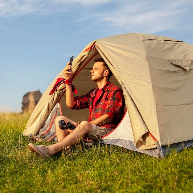 Man in camping tent bij zonsondergang selfie te nemen Gratis Foto