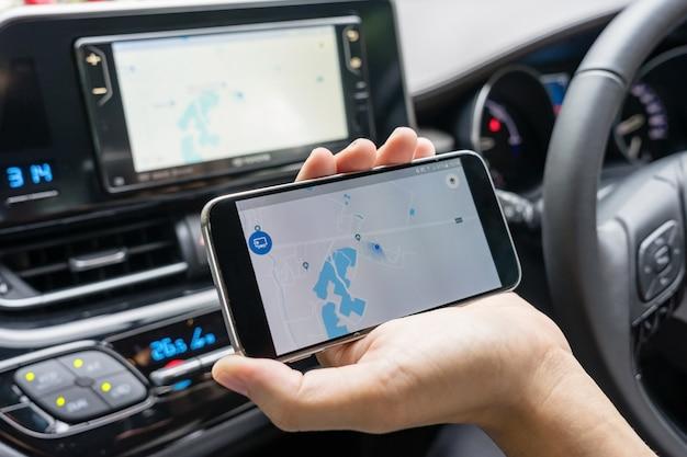 Man in de auto en met zwarte mobiele telefoon met kaart gps navigatie, afgezwakt bij zonsondergang. Premium Foto