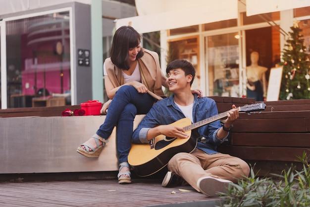 Man in de liefde speelt gitaar zittend op de vloer zijn vriendin Gratis Foto