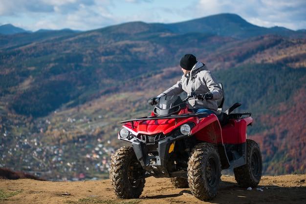 Man in de winterkleren op een rode quad bike op een bergtop Premium Foto