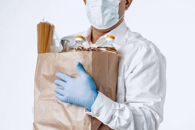 Man in een beschermende medische masker met een zak van een supermarkt Premium Foto
