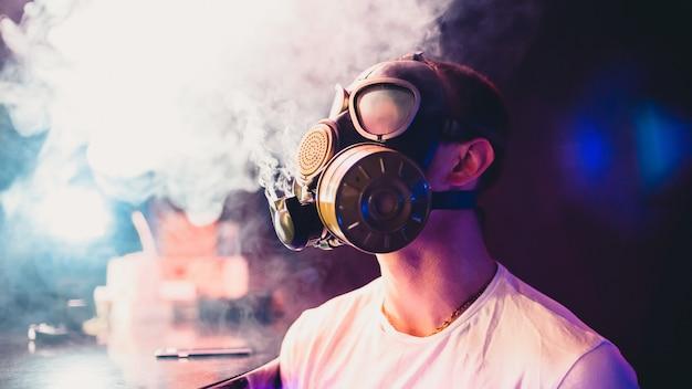 Man in een gasmasker een waterpijp roken en rook blazen Premium Foto
