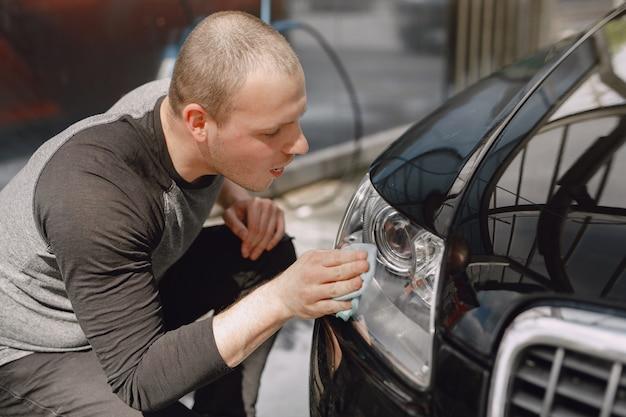 Man in een grijze trui veegt een auto in een wasstraat af Gratis Foto