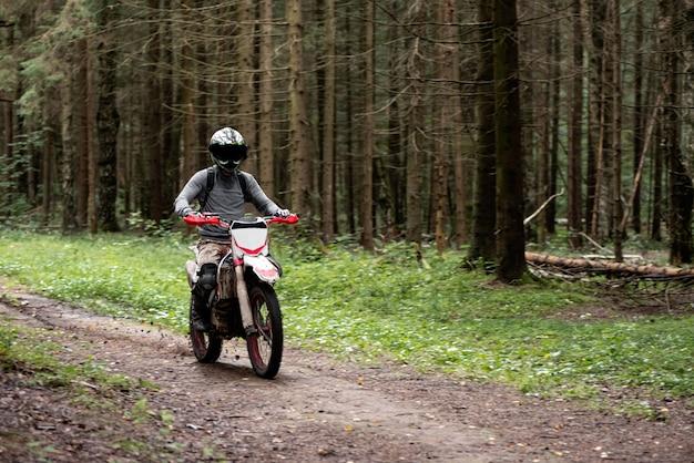 Man in een helm op een motorfiets rijdt op een onverharde weg in het bos Premium Foto