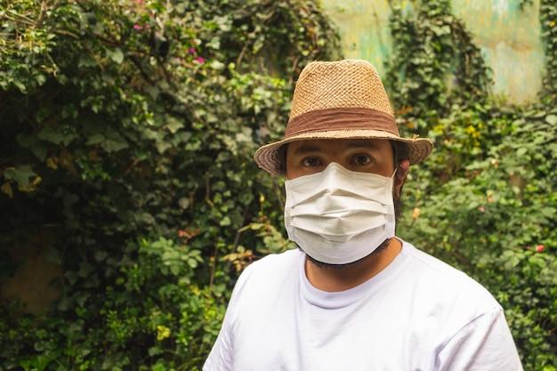 Man in een hoed en een wit overhemd met een gezichtsmasker ter bescherming tegen stof en coronavirus Gratis Foto